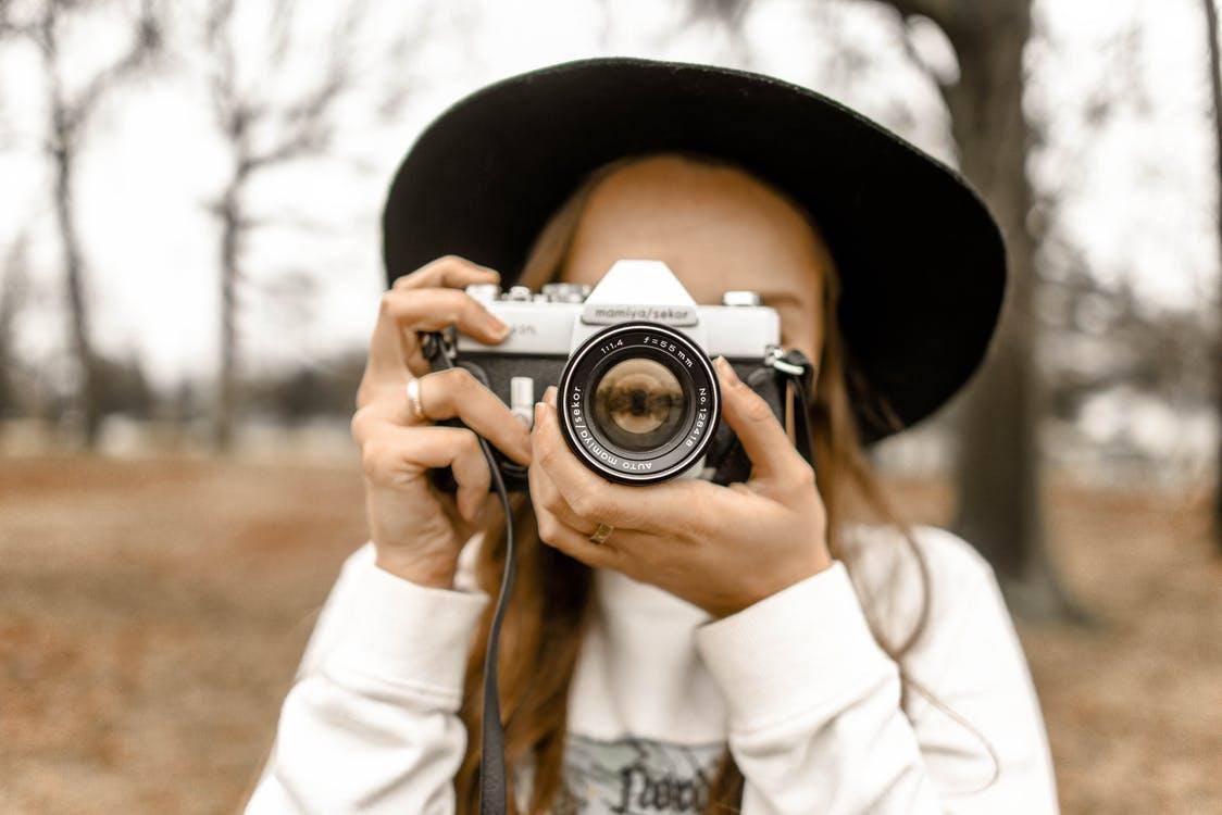 Mädchen mit Hut und Kamera im Wald